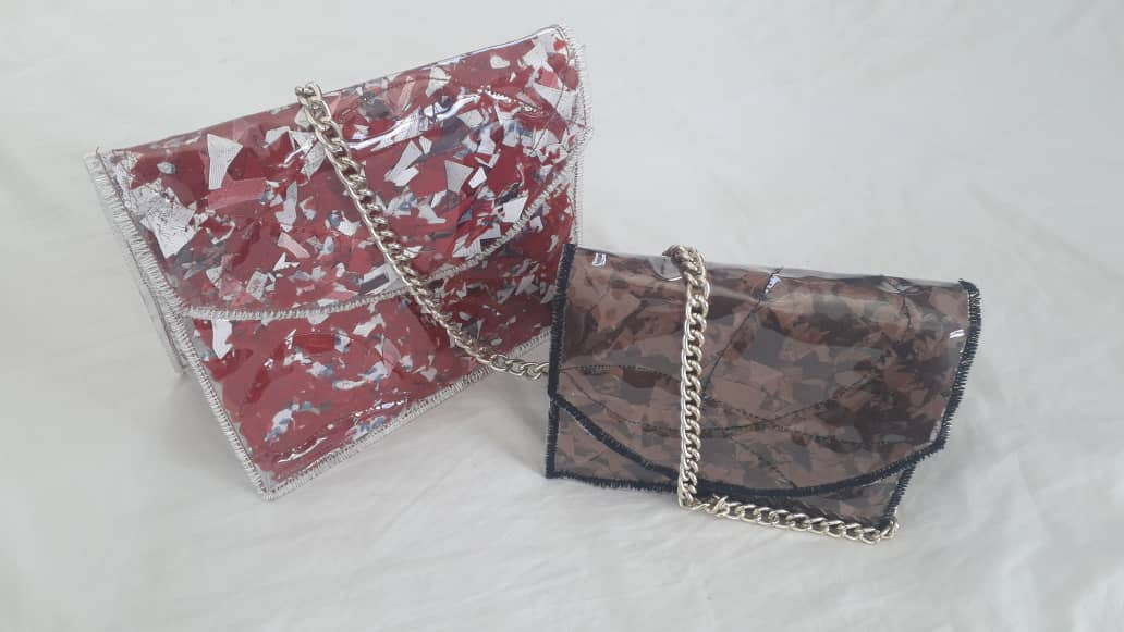 Two clutch bags in front of a white background. One is a red and white clutch bag with a plastic/PVC covering and a metal chain while the other is a brown bag with a plastic/PVC covering, black lining and a metal chain.