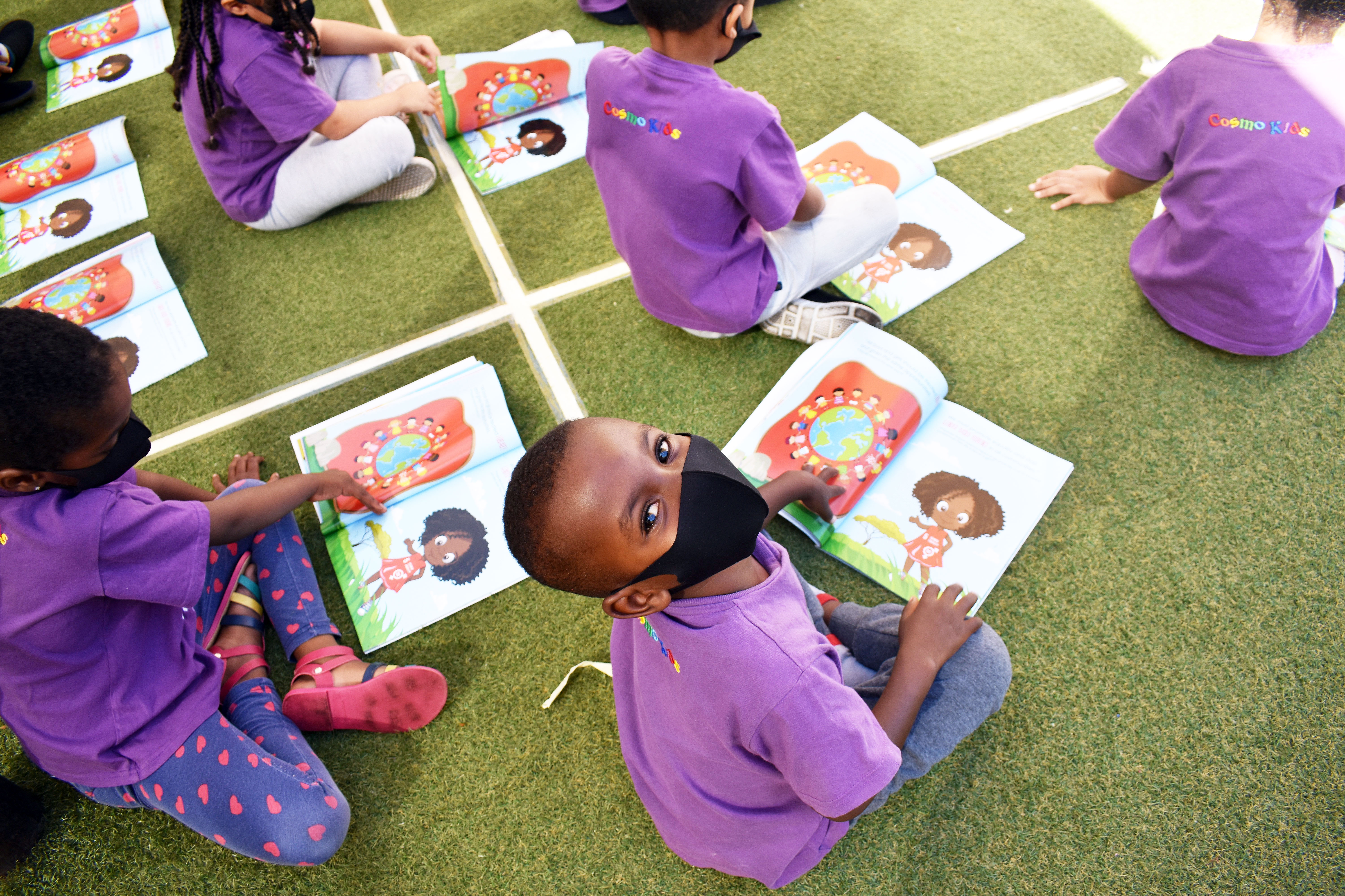 A young child seated on grass with a black mask on surrounded by other learners