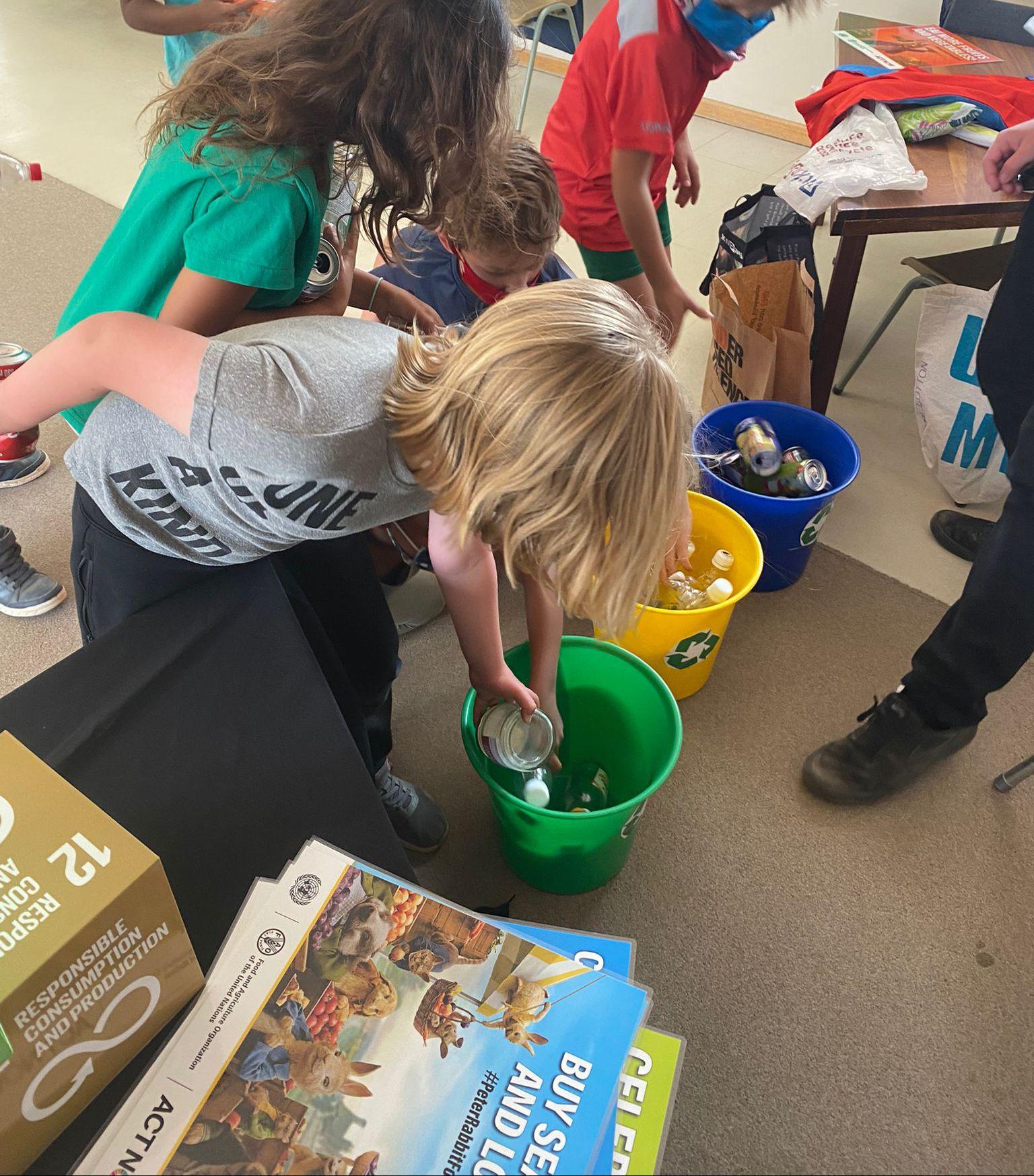 Children sort materials in recycling bins