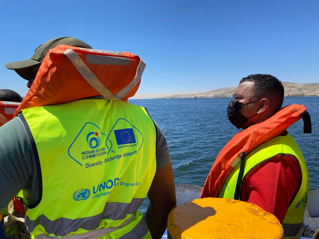 Image shows two men in hi-vis and life jackets on a boat looking out to sea