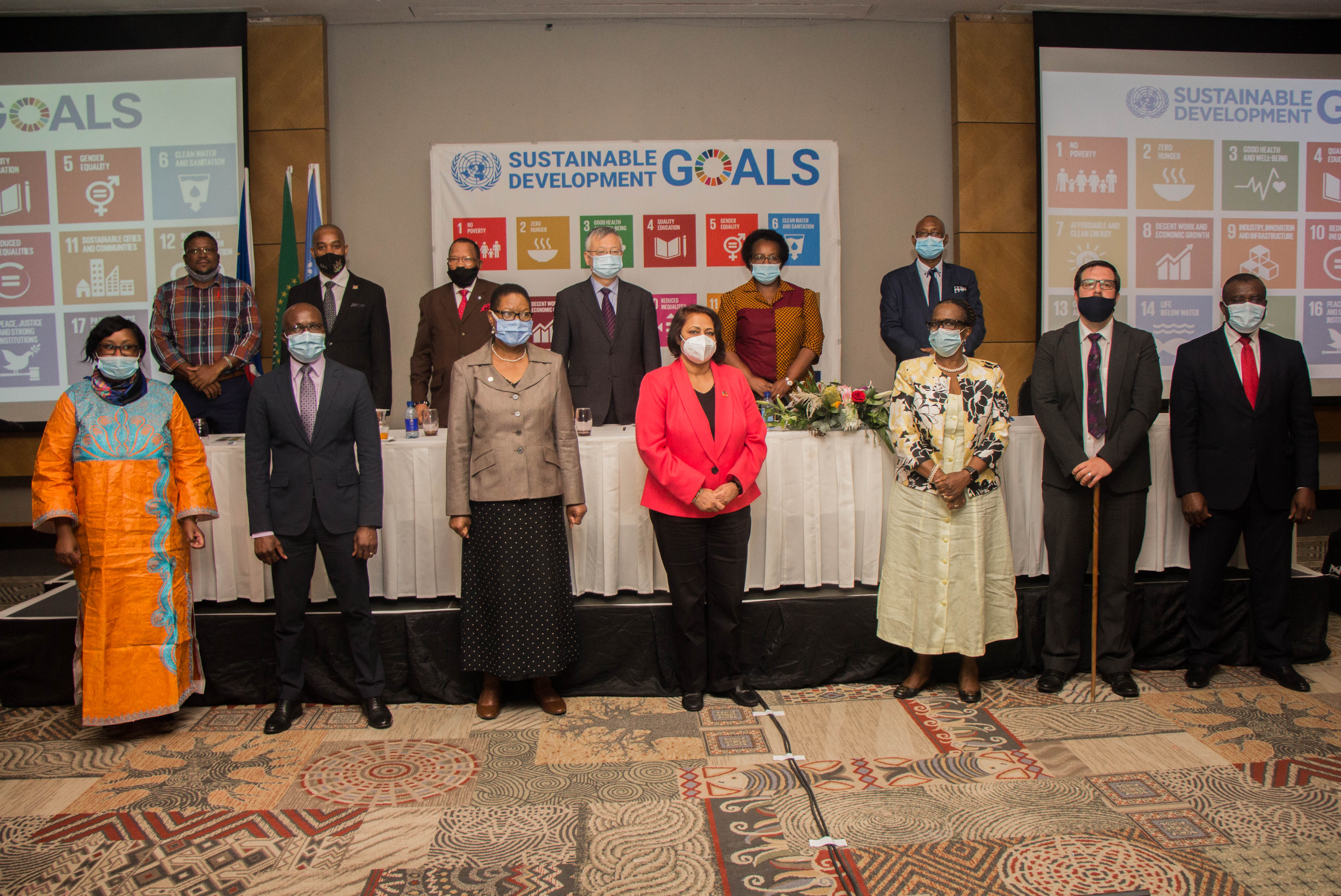 Image shows two rows of dignitaries standing infront of an image of the UN's SDGs
